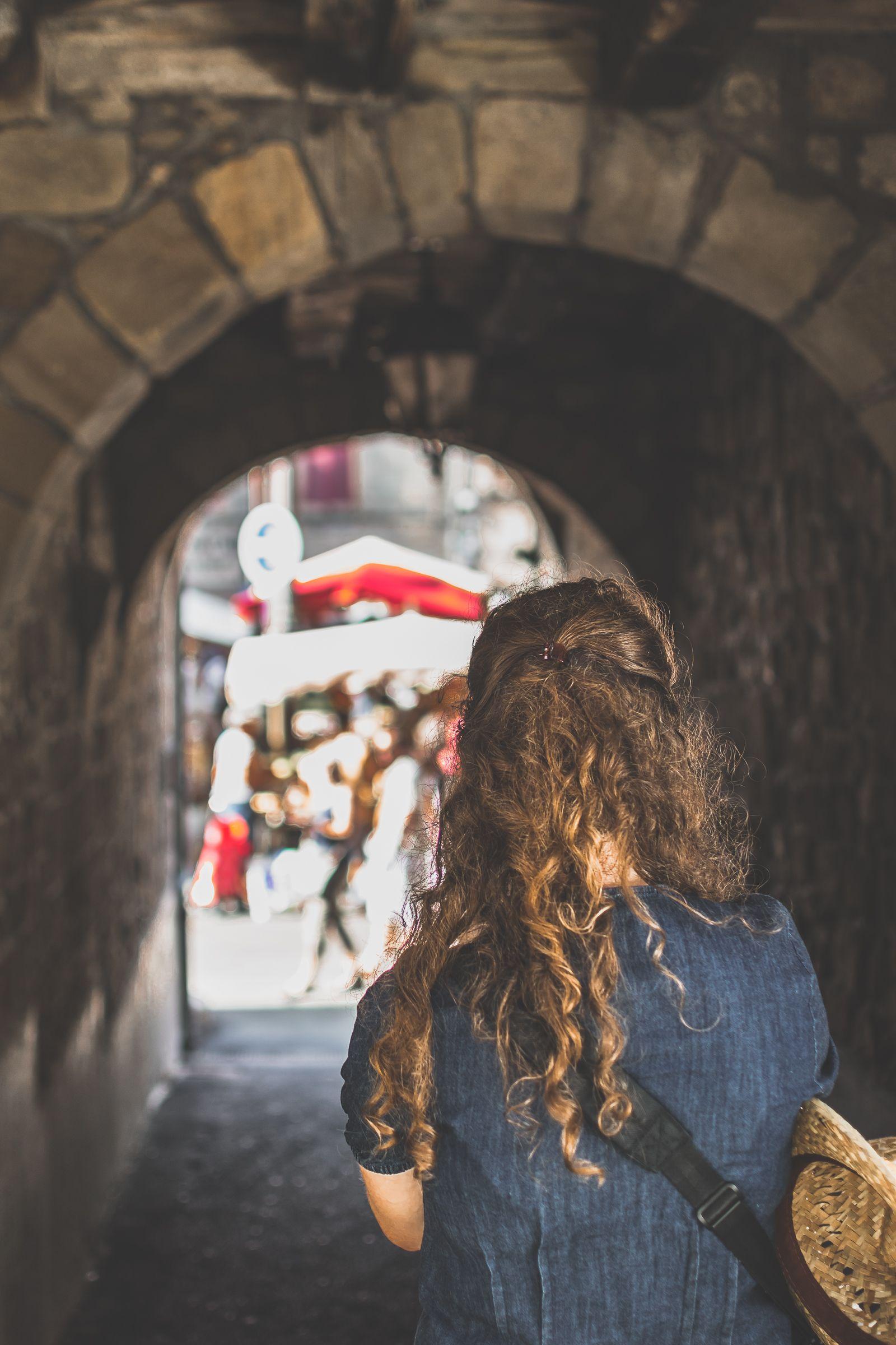 femme sous une arche de pierre